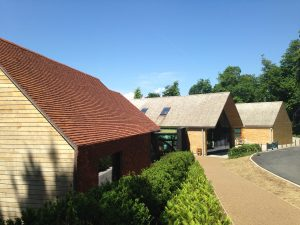 view of two buildings completed in cedar shakes and one in tiles by Kingsley Roofing