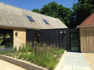 photo shows a view of completed cedar shake roof, pitched tiled roof and standing seam zinc cladding completed by Kingsley Roofing in Chichester