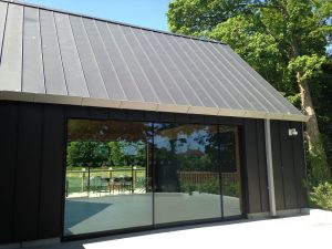 Pitched standing seam Zinc roof and black Zinc vertical cladding completed by Kingsley Roofing at the open air museum in Chichester.